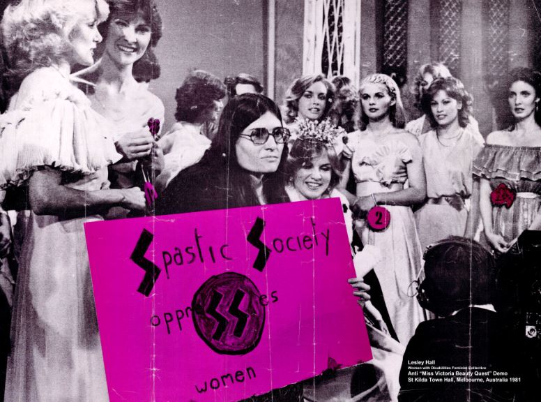 "Lesley Hall at a beauty contest holding a large poster with wording ""Spastic Society Oppresses Women"", behind Lesley are a group of beauty contestants standing and smiling."