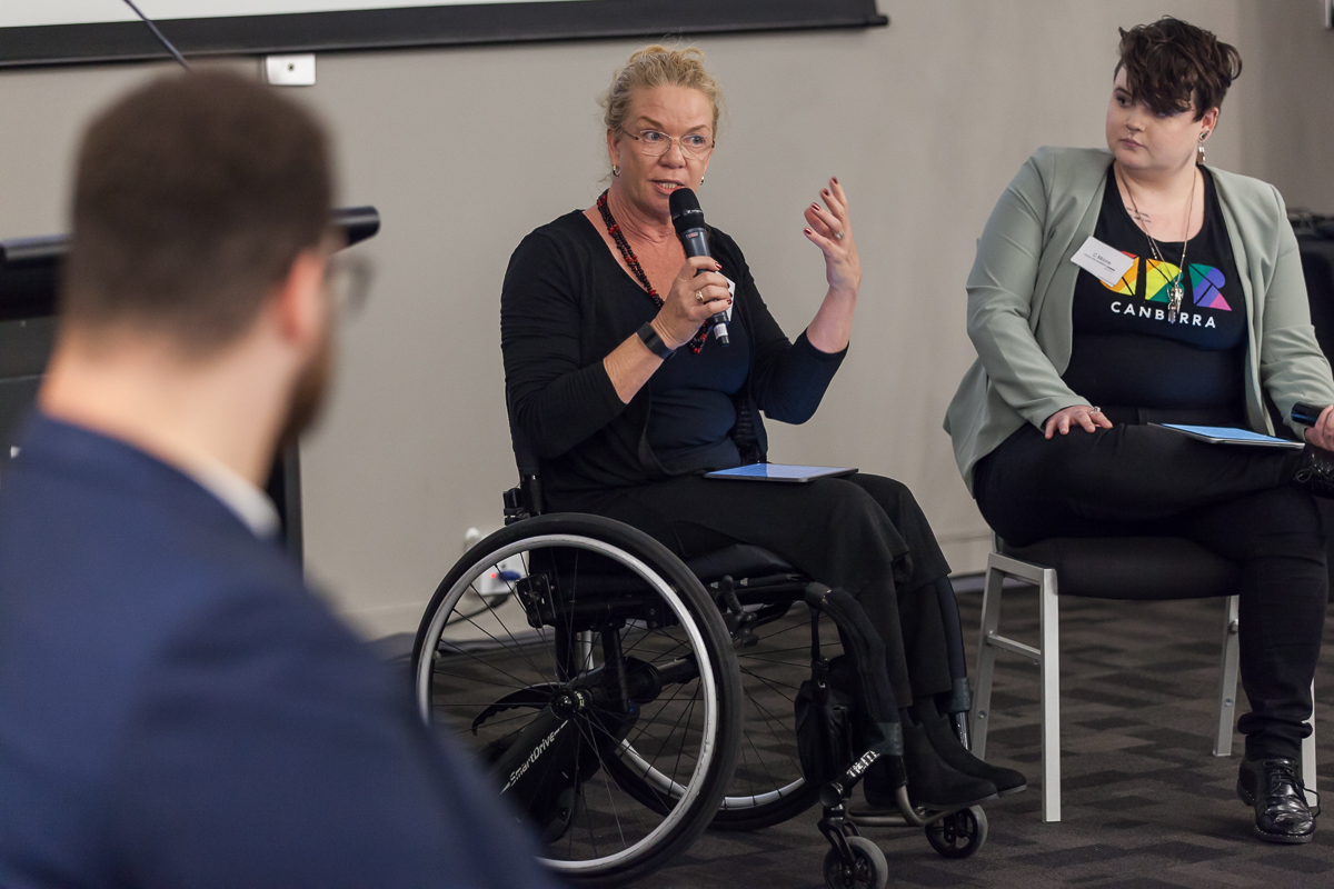 AFDO President, Liz Reid in a wheelchair, speaking into a microphone at our Advocacy Conference.