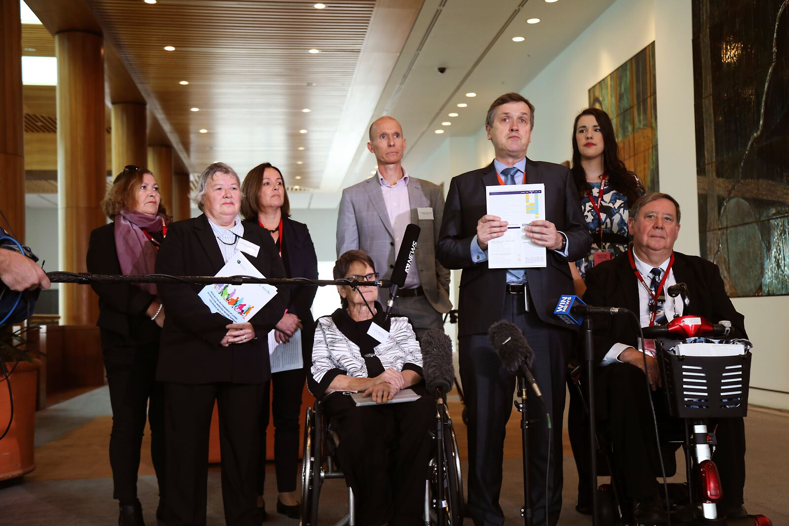 Disability advocates & researchers in a group addressing the media. At the front is AFDO CEO, Ross Joyce speaking to the media.