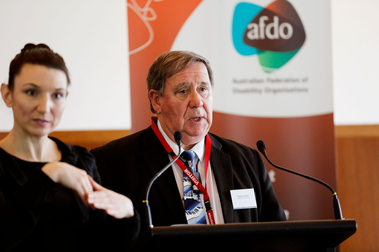 Vice President, Trevor Carroll standing at lectern, speaking into microphone. On the left of Trevor is an Auslan interpreter, and behind Trevor is the AFDO Banner with the AFDO logo.