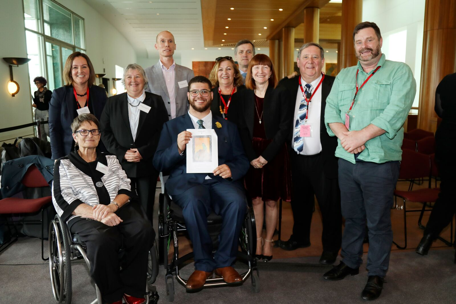 Group photo of 10 people smiling at the camera, in the centre is Jordon Steele-John holding one of the DSP Reports.