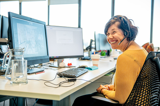 woman sitting at desk with computer in front of her. She has a telephone headset on and is smiling.