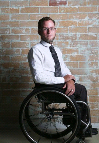 Geoff Trappett sitting in wheelchair and facing camera.