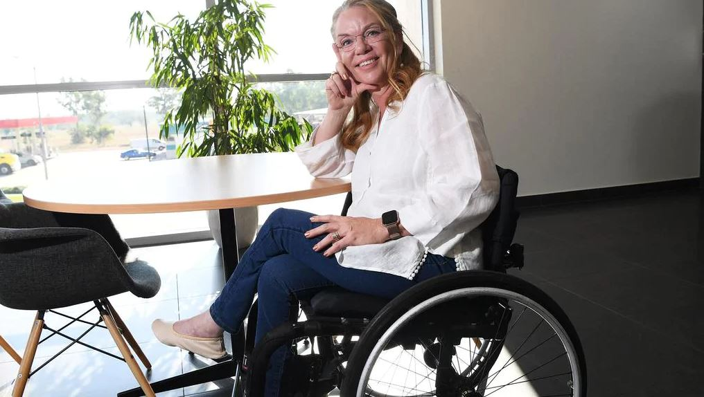 Liz Reid wearing a white shirt and blue jeans, sitting in a wheelchair and smiling at the camera.